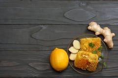 Fundo saudável mel, favo de mel, limão, chá, gengibre na tabela de madeira escura Vista superior com espaço da cópia Imagens de Stock