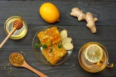 Fundo saudável mel, favo de mel, limão, chá, gengibre na tabela de madeira escura Vista superior com espaço da cópia Imagem de Stock