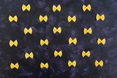 Fundo seco da massa Feche a massa crua do farfalle no fundo escuro Teste padrão liso Vista superior Fotos de Stock Royalty Free