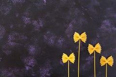 Fundo seco da massa Feche a massa crua do farfalle no fundo escuro Teste padrão liso Vista superior Imagem de Stock