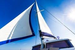 Fundo surpreendente do barco e da vela de navigação sob a luz solar imagens de stock royalty free