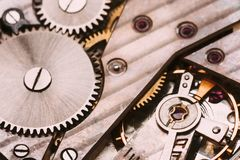 Fundo velho do maquinismo de relojoaria Mecanismo do relógio de pulso de disparo com Gray And Golden Gears fotografia de stock royalty free