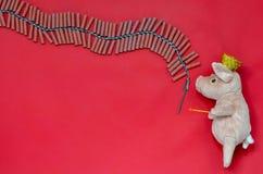 Fundo vermelho da boneca do porco que mantém o fósforo pronto para iluminar foguetes foto de stock