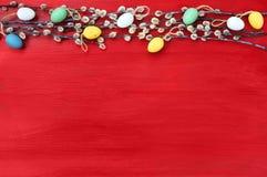 Fundo vermelho de easter Ramo do salgueiro e ovos da páscoa decorativos no fundo vermelho Vista superior Fotos de Stock Royalty Free