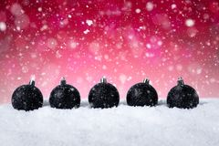 Fundo vermelho do Natal - bolas pretas decoradas na neve com flocos de neve e estrelas Imagens de Stock Royalty Free