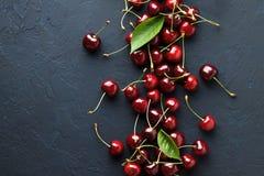 Fundos da baga com as cerejas doces maduras frescas na obscuridade - pedra azul Foto de Stock