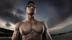 Fundos do esporte Posi??o atl?tica nova do nadador perto do rio do por do sol fotografia de stock royalty free