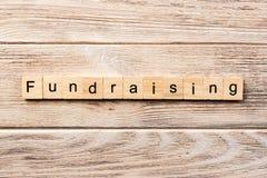 Fundraising ord som är skriftligt på träsnittet fundraising text på tabellen, begrepp arkivfoton