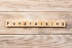 Fundraising word written on wood block. fundraising text on table, concept.  stock photos