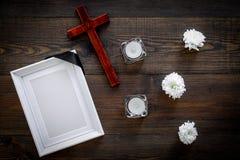funeral Модель-макет портрета покойного, покойника Рамка с черной лентой около цветков, свечей и креста дальше стоковая фотография