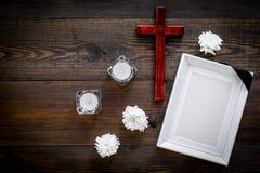 funeral Модель-макет портрета покойного, покойника Рамка с черной лентой около цветков, свечей и креста дальше стоковые фото
