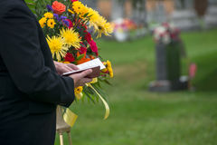 Funeral, Burial Service, Death, Grief. A pastor or minister reads from the Bible during a funeral burial memorial service at a cemetery. Death and grief are a