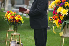 Funeral, Burial Service, Death, Grief. A pastor or minister reads from the Bible during a funeral burial memorial service at a cemetery. Death and grief are a royalty free stock photos