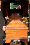 Funeral with casket carried by coffin bearer. Dolor - Funeral with coffin on a cemetery, the casket carried by coffin bearer Royalty Free Stock Photos
