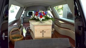 Funeral casket in a hearse or chapel or burial at cemetery. Closeup shot of a funeral casket in a hearse or chapel or burial at cemetery stock footage