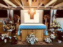 A funeral service is prepared in a church with a cross, flowers, and a flag. A funeral is a ceremony connected with the burial, cremation, or interment of a stock photos
