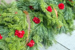 Solemn funeral coniferous garland with carnation flowers and St. George ribbon. Funeral coniferous garland with carnation flowers and St. George ribbon on the royalty free stock photo