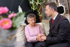 Funeral director comforting woman. Funeral director comforting women funeral royalty free stock photos