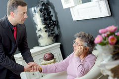 Funeral director holding hand elderly lady. Funeral director holding hand of elderly lady royalty free stock photo