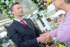 Funeral director shaking hands with elderly woman. Funeral director shaking hands with elderly women shaking stock photos