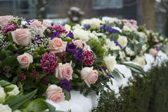 Funeral flowers arrangement in the snow on a cemetery Royalty Free Stock Photography