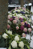 Funeral flowers arrangement in the snowon a cemetery. Several funeral flowers arrangements in the snow on a hedge at the cemetery royalty free stock image