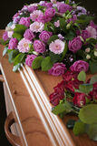 Funeral flowers on a casket. Pink flower arrangement and red roses on a wooden casket Royalty Free Stock Photos