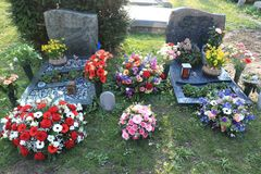 Funeral flowers on graves. Various funeral flowers and sympathy bouquets on a graveyard royalty free stock image