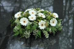 Funeral flowers on a tomb. White funeral flowers on a grey marble tomb stock images