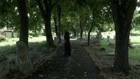 Funeral gothic widow woman in black holding a crown in hand walking in old cemetery alley. Funeral gothic widow woman in black holding a crown in hand walking in stock video