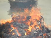 Funeral pyre with fire wood and flames at Cremation grounds. Funeral pyre with firewood and flames at Cremation grounds in Manikarnika Ghat stock photos