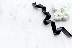 Free Funeral Symbols. White Flower Near Black Ribbon On White Stone Background Top View Copy Space Royalty Free Stock Photography - 132310357