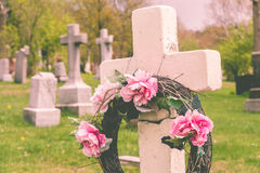 Funeral wreath with pink flower on a cross. Stock Photos