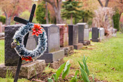 Funeral wreath with red flowers on a cross, in a cemetary. Funeral wreath with red flowers on a cross, in a cemetary, with many headstones in the background stock images