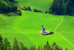 Funes_1. Church surrounded by greenery, Dolomiti mountains Stock Image