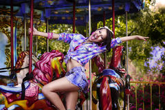 Funfair. Cheerful Woman in Amusement Park on Carousel. Enjoyment. Happy Girl in Amusement Park smiling Stock Photo