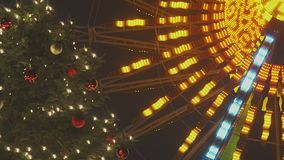 Funfair Christmas Tree. Decorated Christmas Tree At Night With Illuminated Ferris Wheel Spinning And Blinking In The Background In Slow Motion stock video
