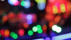 Funfair fairground lights Night colors of the amusement park defocussed stock footage, video, clip, film. Disco lights funfair fairground ride synthwave stock video footage