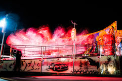 Funfair Ride At Night. Funfair ride in an amusement park at night with moving lights of a small town. Photo Taken At: 2015-08-25 Royalty Free Stock Images