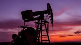 Fungerande fossila bränslenbrunn som profileras på solnedgånghimmel royaltyfri bild