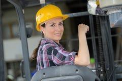 Fungerande gaffeltruck för kvinnlig arbetare i sändande gård arkivbild