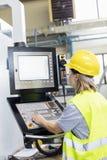 Fungerande maskineri för kvinnlig arbetare på kontrollbordet i fabrik royaltyfri bild