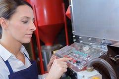 Fungeringsmaskin för kvinnlig arbetare i fabrik royaltyfri foto