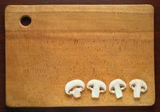 Funghi affettati del fungo prataiolo su un piatto di legno fotografia stock libera da diritti
