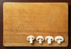 Funghi affettati del fungo prataiolo su un piatto di legno fotografie stock