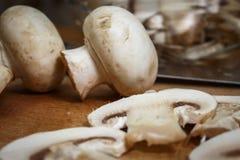 Funghi affettati nella cucina su un bordo Fotografie Stock Libere da Diritti