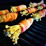 Funghi di Enoki avvolti in bacon sulla griglia Fotografia Stock