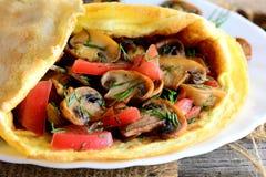 Funghi ed idea dell'omelette dei pomodori Omelette casalinga farcita con i funghi, i pomodori e l'aneto su un piatto e su una tav fotografie stock libere da diritti