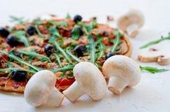 Funghi freschi sulla tavola bianca con lo spazio della copia libera dalla destra Pizza della verdura con le verdure, olive, rucol Immagine Stock