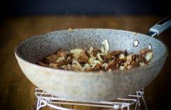 Funghi organici della foresta fritti con le cipolle in una pentola fotografia stock libera da diritti